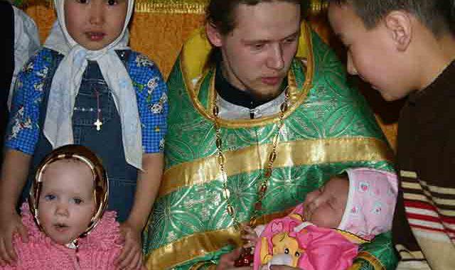 священник держит на руках малыша, Сергий Клинцов
