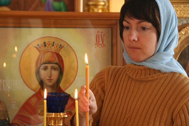 Женщина в храме ставит свечу