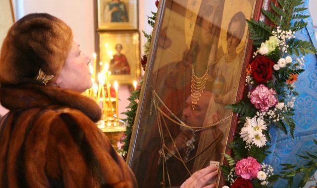 Женщина молится у чудотворной иконы